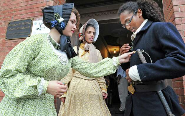 Imani McCalmon,17, left, and Irini Beshello, 17, help Shawn Anthony Sundown, 19, right, with his U.S. Colored Troops uniform as they welcome visitors to the Annual Young Abolitionist Teen Scholars' Institute Open House at the historic Stephen and Harriet Myers Residence Thursday July 30, 2015 in Albany, NY.  (John Carl D'Annibale / Times Union) Photo: John Carl D'Annibale / 10032837A