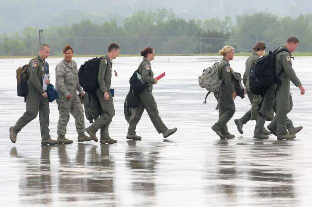Air guard members walk out to a C-130 airplane waiting for patients during an exercise at the Stratton Air National Guard Base on Thursday, July 30, 2015 in Glenville, N.Y.  The annual exercise required as part of the federal National Disaster Medical System in which hospital patients and nursing home residents are evacuated from disaster areas to regions in which they can be cared for in government and civilian hospitals and health care facilities. The exercise involves simulated patients being moved from civilian facilities to Stratton Air National Guard Base. (Lori Van Buren / Times Union) Photo: Lori Van Buren / 10032829A