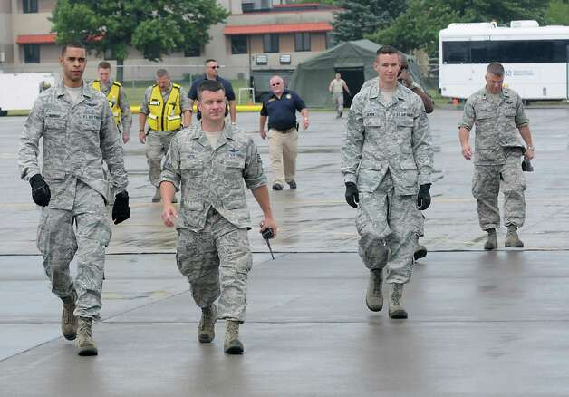 U.S. Air Force members walk out to a C-130 airplane waiting for patients during an exercise at the Stratton Air National Guard Base on Thursday, July 30, 2015 in Glenville, N.Y.  The annual exercise required as part of the federal National Disaster Medical System in which hospital patients and nursing home residents are evacuated from disaster areas to regions in which they can be cared for in government and civilian hospitals and health care facilities. The exercise involves simulated patients being moved from civilian facilities to Stratton Air National Guard Base. (Lori Van Buren / Times Union) Photo: Lori Van Buren / 10032829A