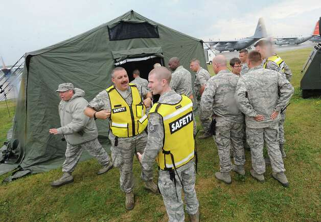 Air guard members wait outside a tent with patients in it before transporting them to a C-130 airplane during an exercise at the Stratton Air National Guard Base on Thursday, July 30, 2015 in Glenville, N.Y.  The annual exercise required as part of the federal National Disaster Medical System in which hospital patients and nursing home residents are evacuated from disaster areas to regions in which they can be cared for in government and civilian hospitals and health care facilities. The exercise involves simulated patients being moved from civilian facilities to Stratton Air National Guard Base. (Lori Van Buren / Times Union) Photo: Lori Van Buren / 10032829A