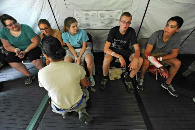 Civil Air Patrol members act as patients and wait to be transported to a C-130 airplane during an exercise at the Stratton Air National Guard Base on Thursday, July 30, 2015 in Glenville, N.Y.  The annual exercise required as part of the federal National Disaster Medical System in which hospital patients and nursing home residents are evacuated from disaster areas to regions in which they can be cared for in government and civilian hospitals and health care facilities. The exercise involves simulated patients being moved from civilian facilities to Stratton Air National Guard Base. (Lori Van Buren / Times Union) Photo: Lori Van Buren / 10032829A