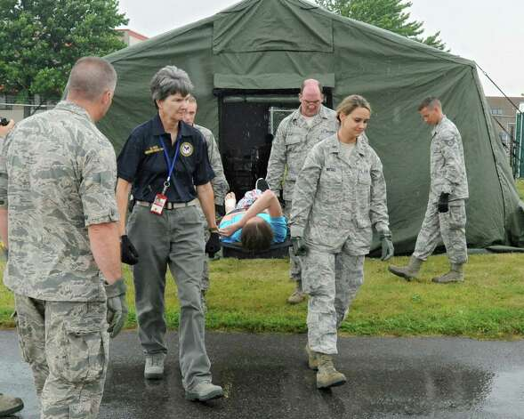 Civil Air Patrol members acting as patients are transported to a bus which will take them out to a C-130 airplane during an exercise at the Stratton Air National Guard Base on Thursday, July 30, 2015 in Glenville, N.Y.  The annual exercise required as part of the federal National Disaster Medical System in which hospital patients and nursing home residents are evacuated from disaster areas to regions in which they can be cared for in government and civilian hospitals and health care facilities. The exercise involves simulated patients being moved from civilian facilities to Stratton Air National Guard Base. (Lori Van Buren / Times Union) Photo: Lori Van Buren / 10032829A