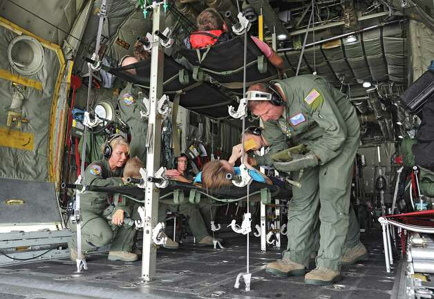 Air guard members from Scotia and Tennessee tend to civil air patrol members acting as patients on a C-130 airplane during an exercise at the Stratton Air National Guard Base on Thursday, July 30, 2015 in Glenville, N.Y.  The annual exercise required as part of the federal National Disaster Medical System in which hospital patients and nursing home residents are evacuated from disaster areas to regions in which they can be cared for in government and civilian hospitals and health care facilities. The exercise involves simulated patients being moved from civilian facilities to Stratton Air National Guard Base. (Lori Van Buren / Times Union) Photo: Lori Van Buren / 10032829A