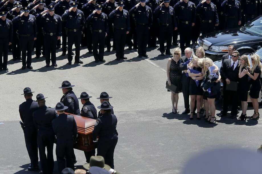 Members of the Lunger family (right) console one another as the coffin carrying the remains of Sgt. Scott Lunger is carried to the hearse. Thousands attended the funeral for slain Hayward, Calif. police Sgt. Scott Lunger at the Oracle Arena in Oakland Thursday July 30, 2015. Photo: Brant Ward, The Chronicle