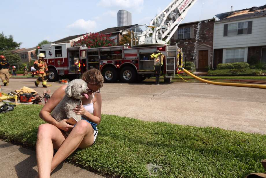 "Stacie Zuber comforts ""Lucy"" at the scene of a three alarm fire in the 5800 block of Valley Forge. Zuber's neighbor lost at least one of her three dogs in the fire that damaged five or six units. / Photo: Jon Shapley 