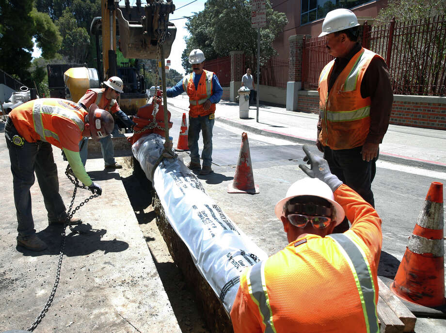 A construction crew lowers a section of an underground water pipeline behind San Francisco General Hospital as part of the city Public Utility Commission's $4.8 billion program to retrofit the water system for seismic safety. Photo: Paul Chinn / Paul Chinn / The Chronicle / ONLINE_YES