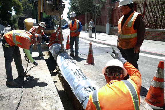 A construction crew lowers a section of an underground water pipeline behind San Francisco General Hospital as part of the city Public Utility Commission's $4.8 billion program to retrofit the water system for seismic safety.