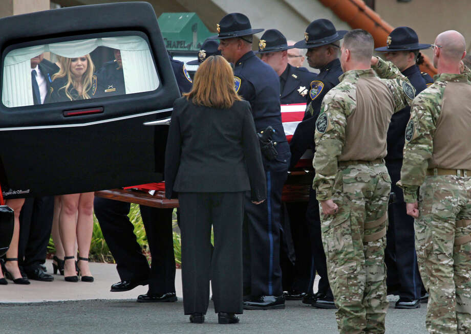 The casket of police Sgt. Scott Lunger is placed in a hearse as his daughter Saralyn (seen through door at left) stands by. Photo: Paul Chinn / Paul Chinn / The Chronicle / ONLINE_YES