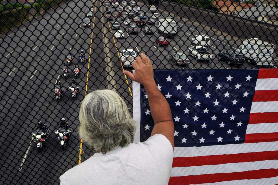 John Medeiros holds up a flag to pay his respects from the Paseo Grande overpass above Interstate 880 in San Lorenzo as the funeral procession begins to pass below. Photo: Loren Elliott / Loren Elliott / The Chronicle / ONLINE_YES