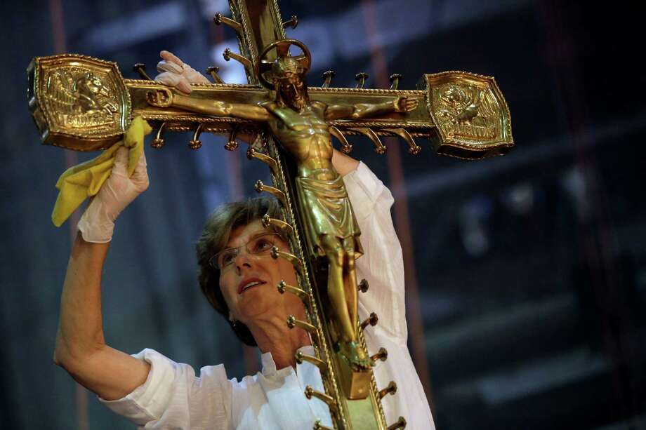 Lucia Popian, president of G&L Popian, cleans and polishes the crucifix on the main altar, Friday, July 17, 2015, as part of the of the ongoing $177 million restoration of St. Patrick's Cathedral in New York. The renovation, done in three phases over three years, started in 2012 and is slated to be finished before the Pope's visit in September 2015. (AP Photo/Mary Altaffer) Photo: Mary Altaffer, STF / Associated Press / AP