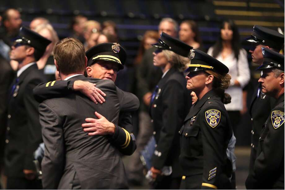 U.S. Rep. Eric Swalwell, left, and a law enforcement officer embrace at the end of a memorial service for Sgt. Scott Lunger at Oracle Arena in Oakland, Calif., Thursday, July 30, 2015. Lunger shot and killed during a traffic stop on July 22. (Ray Chavez/Bay Area News Group via AP, Pool) Photo: Ray Chavez, Associated Press