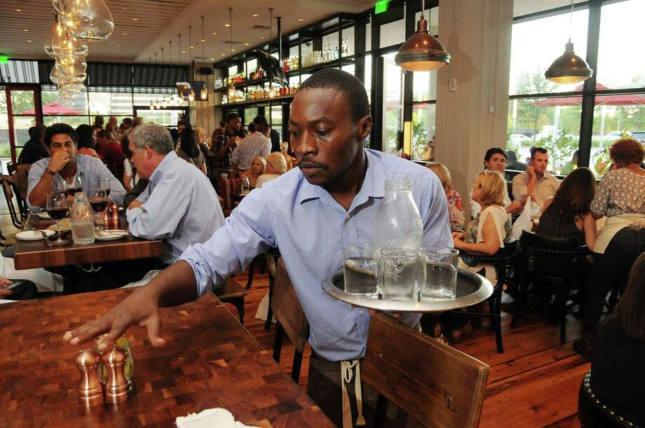 Sabin Naweji clears a table at North Italia, a restaurant near the Galleria. After four months, the new establishment is fully staffed. Houston's restaurant industry is booming, making it tougher to hire all the needed employees. Photo: Dave Rossman, Freelance / Freelalnce