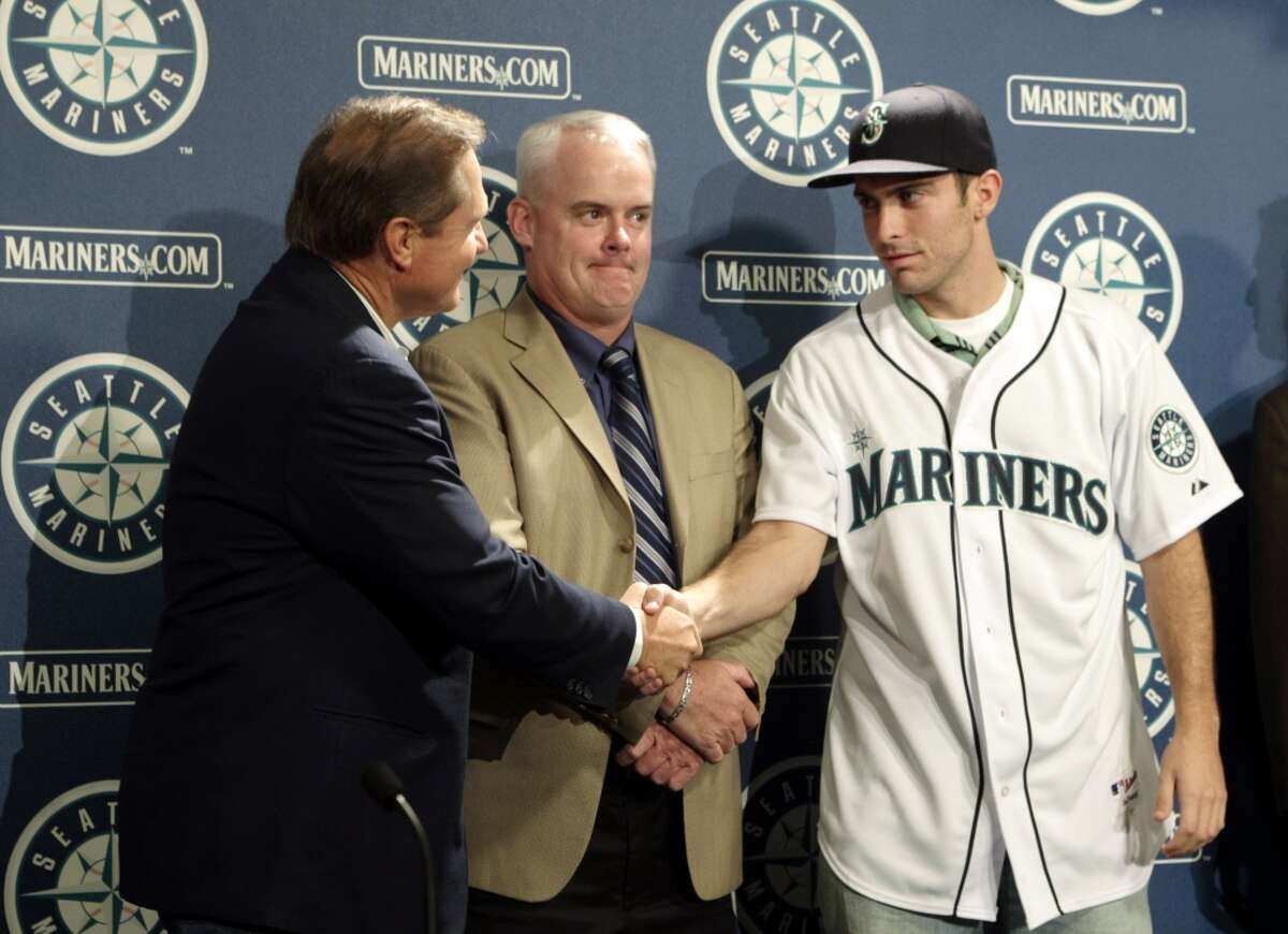 Dustin Ackley, right, the Seattle Mariners' top pick in the 2009 first-year player MLB baseball draft, shakes hands with Scott Boras, his agent, as Mariners' director of amateur scouting Tom McNamara looks on, after Ackley was introduced Monday, Aug. 31, 2009, at Safeco Field in Seattle.
