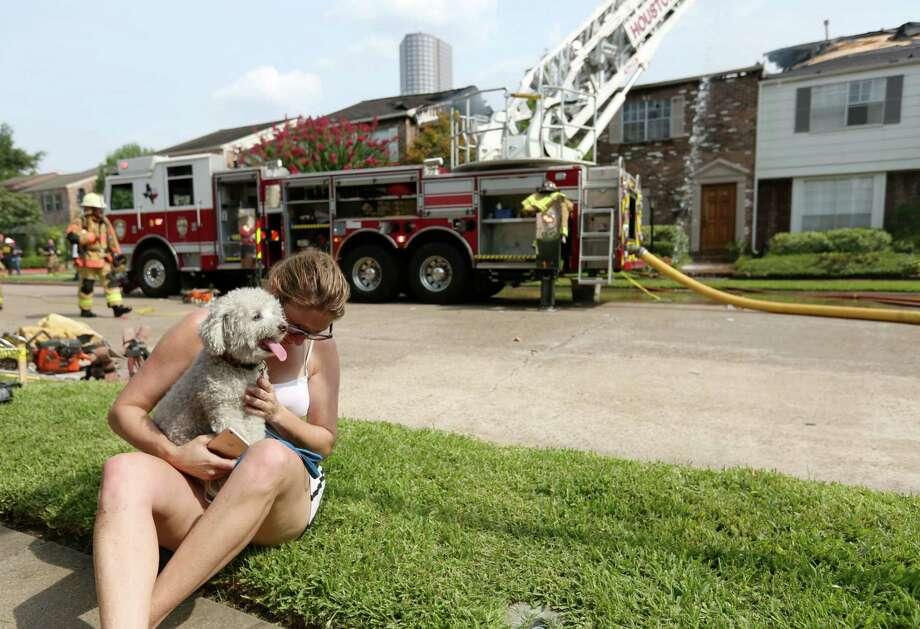 """Stacie Zuber comforts her neighbor's dog, """"Lucy,"""" at the scene of a three-alarm fire in the 5800 block of Valley Forge Thursday, July 30, 2015, in Houston. Zuber's neighbor Dina Ramsey lost at least one of her three dogs in the fire. Photo: Jon Shapley, Houston Chronicle / © 2015 Houston Chronicle"""