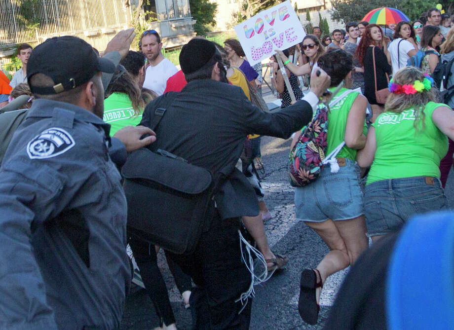 Security forces reach for a man as he tries to stab a woman during Jerusalem's Gay Pride Parade. Police arrested an ultra-Orthodox Jew who served 10 years in prison for a similar attack in 2005. Photo: Sebastian Scheiner /Associated Press / AP
