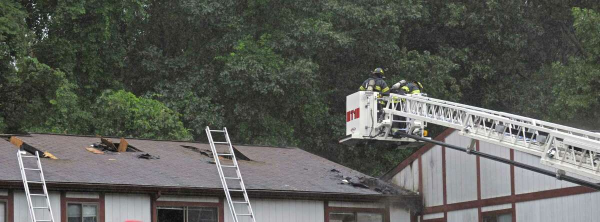 Danbury firefighters work on the roof of a condominium on Candlelight Drive, in Danbury, Conn, on Thursday afternoon, July 30, 2015. Firefighters knocked down an attic fire at the condominium, which began just after 4 p.m.