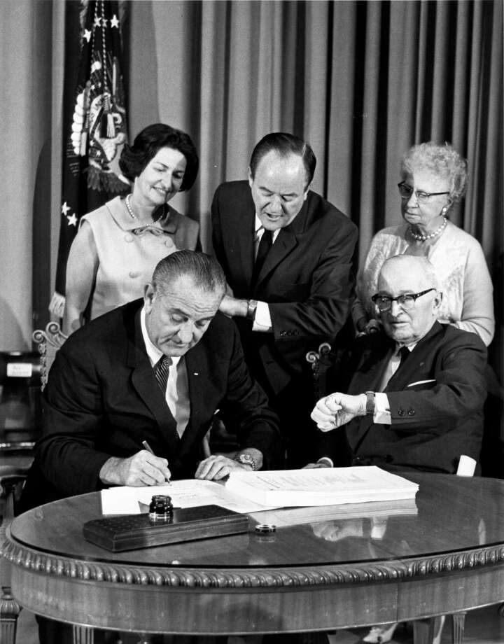 President Lyndon Johnson signs the Medicare bill in 1965 as Vice President Hubert Humphrey and former President Harry Truman check their watches. Lady Bird Johnson and Bess Truman look on. / Associated Press