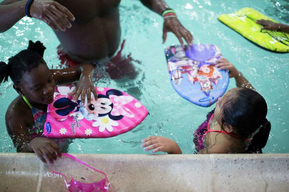 Madison Seymour, left, 8, and Isabella Montalbo, right, 7, hold on to their swimming boards during recent  swimming classes at the Boys & Girls Club in Houston. Photo: Marie D. De Jesus, Staff / © 2015 Houston Chronicle