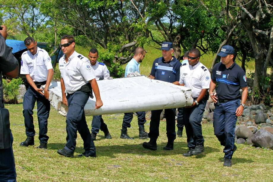 """In this photo dated Wednesday, July 29, 2015, French police officers carry a piece of debris from a plane in Saint-Andre, Reunion Island. Air safety investigators, one of them a Boeing investigator, have identified the component as a """"flaperon"""" from the trailing edge of a Boeing 777 wing, a U.S. official said. Flight 370, which disappeared March 8, 2014, with 239 people on board, is the only 777 known to be missing. (AP Photo/Lucas Marie) Photo: Lucas Marie, STR / Associated Press / AP"""
