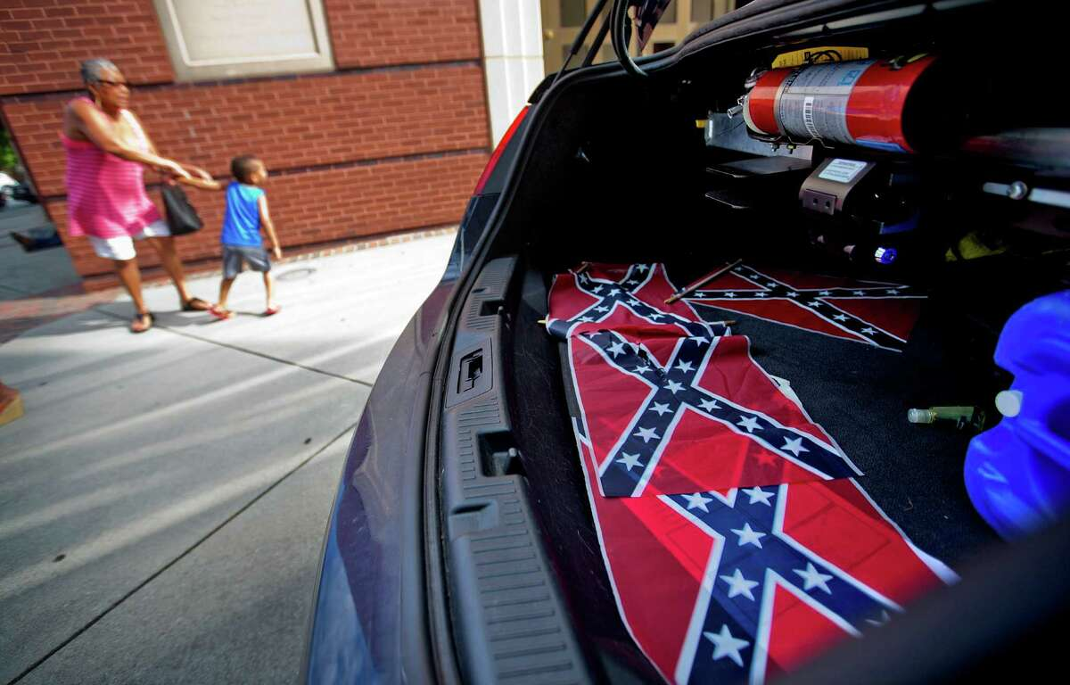 Confederate flags sit in a police car as tourists pass Atlanta's Ebenezer Baptist Church, where Martin Luther King Jr. preached. Also nearby is the home were King lived for the first 12 years of his life.