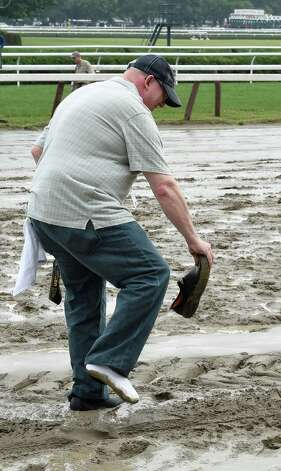 Photographer Joe LaBozetta replaces the shoe that was sucked from his foot in the muddy track Thursday afternoon July 30, 2015, at the Saratoga Race Course in Saratoga Springs, N.Y.    (Skip Dickstein/Times Union) Photo: SKIP DICKSTEIN