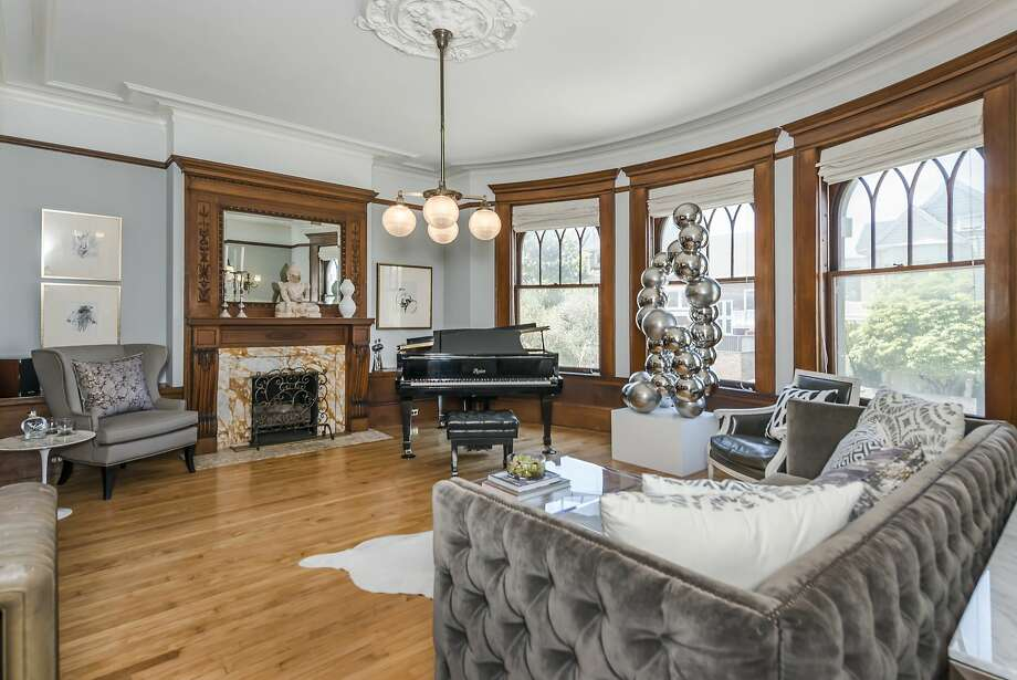 The living room of 880 Ashbury St. features a fireplace with marble surround, ceiling medallion and ornate hardwood details. Photo: Olga Soboleva/Vanguard Propertie