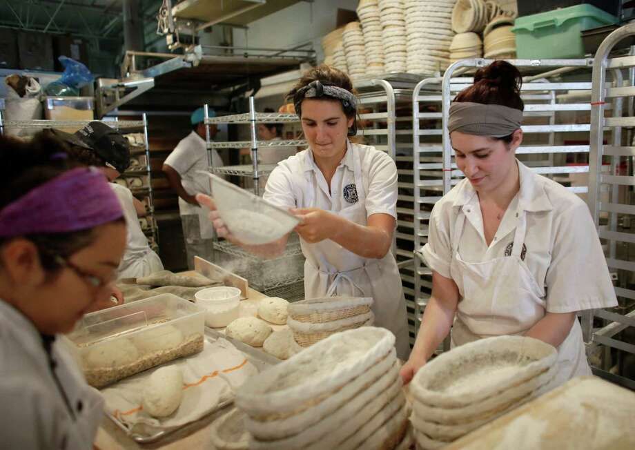 Natasha Portuondo (center) sifts flour over baskets as she and Adina Robles (right) make bread at Zak the Baker, in Miami. The U.S. economy posted a solid rebound in the April-June quarter after a harsh winter, the Commerce Department said Thursday. Photo: Lynne Sladky /Associated Press / AP