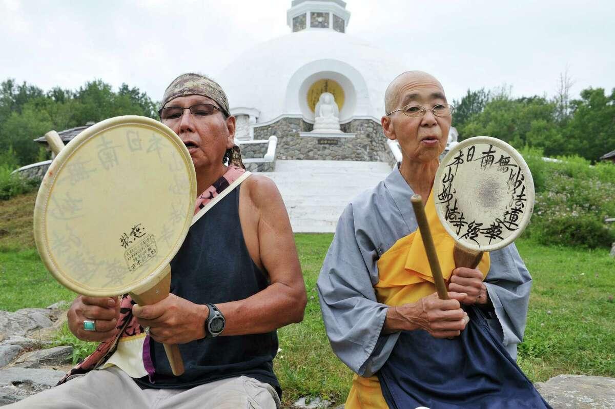Larry Bringing Good, left, and Jun Yasuda, a Buddhist nun, use fan drums outside the Grafton Peace Pagoda on Thursday, July 30, 2015. (Paul Buckowski / Times Union)