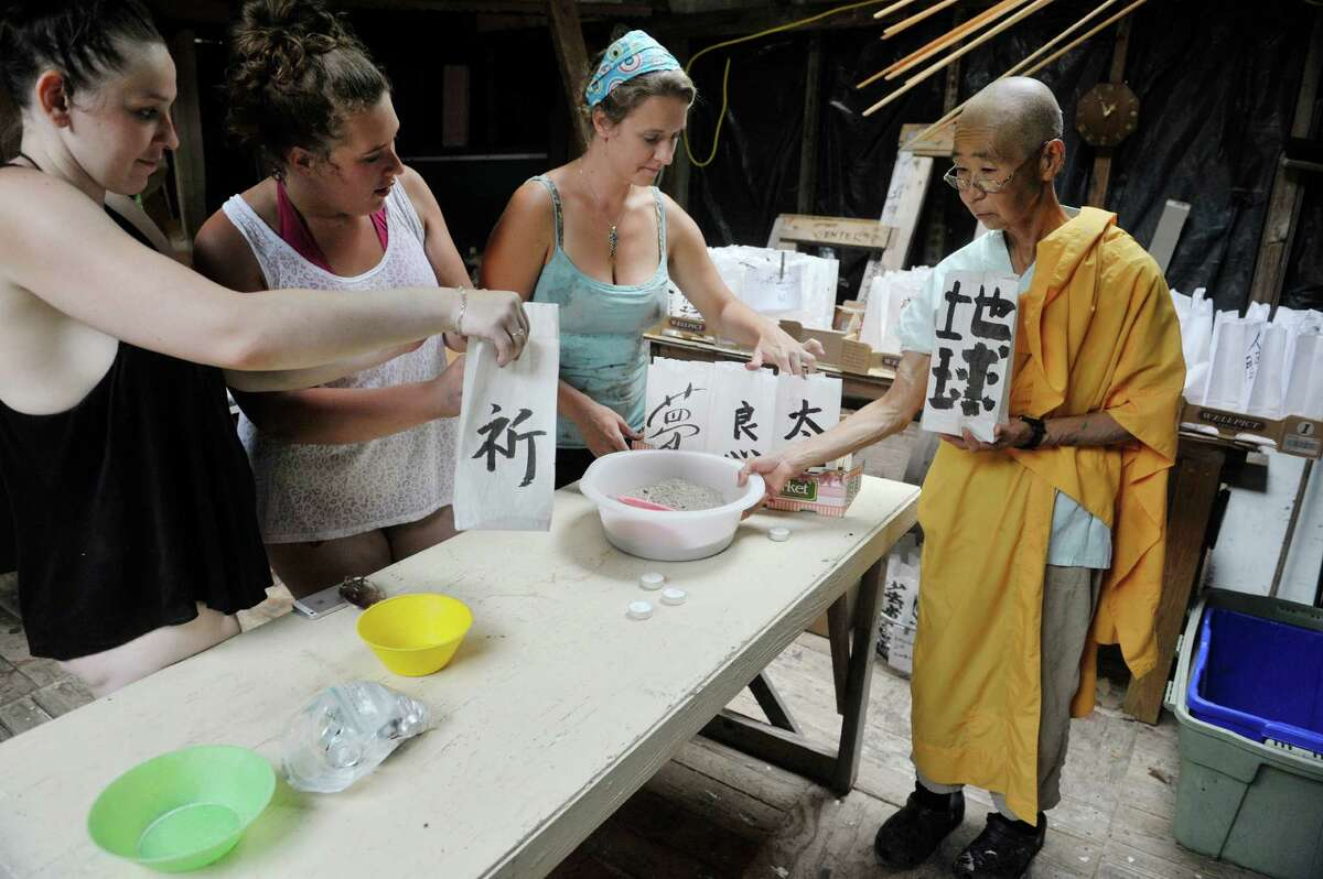 Students, Monique Goodell, left, and Jasmine Rice, second from left, along with their teacher Jeannie O'Neill, third from left, from the Sunrise Opportunity Program in Bennington, VT, work with Jun Yasuda, a Buddhist nun at the Grafton Peace Pagoda on Thursday, July 30, 2015. The women were filling bags with sand and candles as paper lanterns that will be used for the 70th Hiroshima commemoration ceremony being held at the Grafton Peace Pagoda. The Sunrise Opportunity Program is an alternative high school for pregnant and parenting youth. (Paul Buckowski / Times Union)
