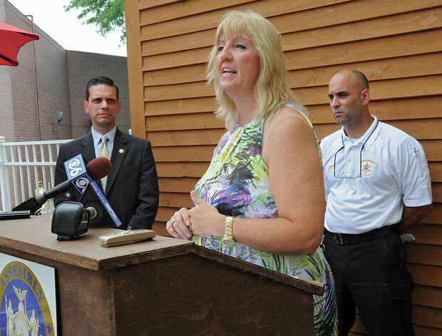 Cindy Barkowski, a parent of a child with Autism, speaks during a press conference announcing that the county is expanding a program that provides emergency bracelets for autistic children who get lost or run away at Puzzles Bakery & Cafe on Thursday, July 30, 2015 in Schenectady, N.Y. Assemblyman Angelo Santabarbara, left, and Schenectady County Sheriff Dominic Dagostino stand behind her. (Lori Van Buren / Times Union) Photo: Lori Van Buren / 10032831A