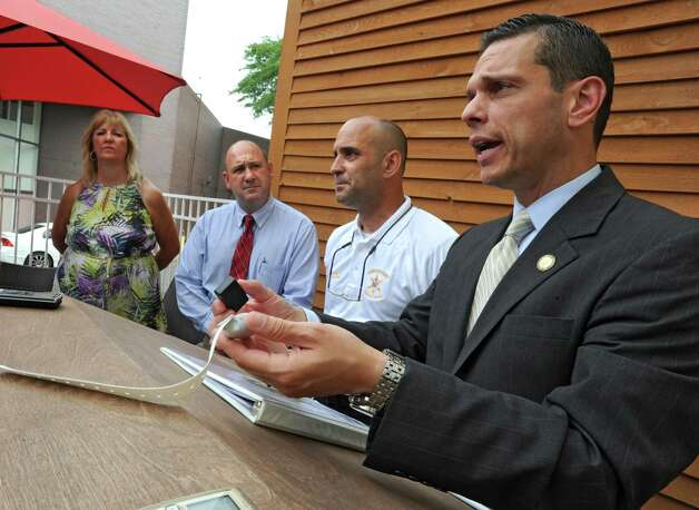 Assemblyman Angelo Santabarbara explains how to check the battery of a bracelet during a press conference announcing that the county is expanding a program that provides emergency bracelets for autistic children who get lost or run away at Puzzles Bakery & Cafe on Thursday, July 30, 2015 in Schenectady, N.Y. Standing in the back from left are Cindy Barkowski, a parent of a child with Autism, Michael Smith, Legislative Director for Autism Action Network and Schenectady County Sheriff Dominic Dagostino. Santabarbara's son was diagnosed with Autism when he was 3. (Lori Van Buren / Times Union) Photo: Lori Van Buren / 10032831A