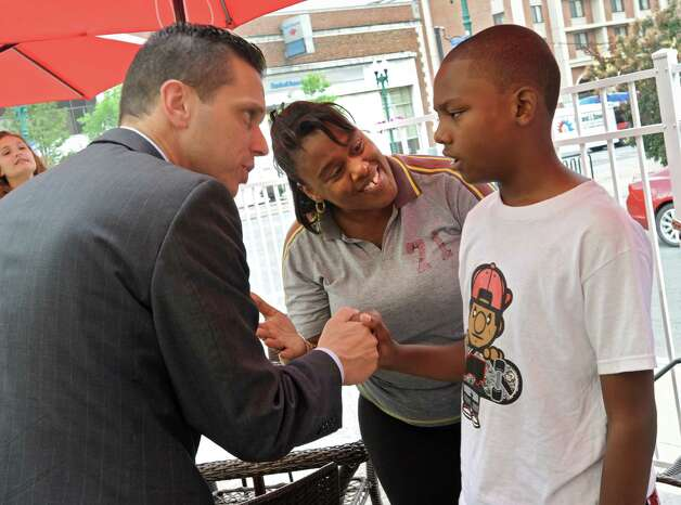Assemblyman Angelo Santabarbara meets Rahmee Delagrandeanse, 11, and his mother Tanisha Harvey of Schenectady, after a press conference announcing that the county is expanding a program that provides emergency bracelets for autistic children who get lost or run away at Puzzles Bakery & Cafe on Thursday, July 30, 2015 in Schenectady, N.Y. Rahmee, who is autistic went missing for about 5 hours once and was found at a nearby McDonalds. (Lori Van Buren / Times Union) Photo: Lori Van Buren / 10032831A