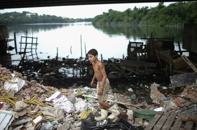 RIO DE JANEIRO, BRAZIL - JULY 29:  A boy looks for items to recycle along the polluted Cunha canal which flows into the notoriously polluted Guanabara Bay, site of sailing events for the Rio 2016 Olympic Games, on July 29, 2015 in Rio de Janeiro, Brazil. The Rio government promised to clean 80 percent of pollution and waste from the bay in time for the games but admits that goal now is unlikely to be reached.  August 5 marks the one-year mark to the start of the Rio 2016 Olympic Games.  (Photo by Mario Tama/Getty Images) ORG XMIT: 566534797 Photo: Mario Tama / 2015 Getty Images