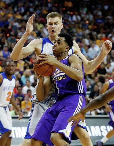 Los Angeles Lakers' D'Angelo Russell, front, drives into New York Knicks' Kristaps Porzingis during the first half of an NBA summer league basketball game Monday, July 13, 2015, in Las Vegas. (AP Photo/John Locher) ORG XMIT: NVJL137 Photo: John Locher / AP