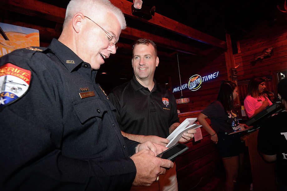 Jefferson County Sheriff Department officer s Rod Carroll and Marcus McLellan talk as they get ready to begin collecting donations. Local police officers helped serve the public in a different way Thursday night at Texas Roadhouse in Port Arthur. Officers waited on  diners and collected donations during the eighth annual Tip-A-Cop event,  whose proceeds benefit Special Olympics Texas. Similar events are taking place at a total of 47 Texas Roadhouse restaurants across the state.