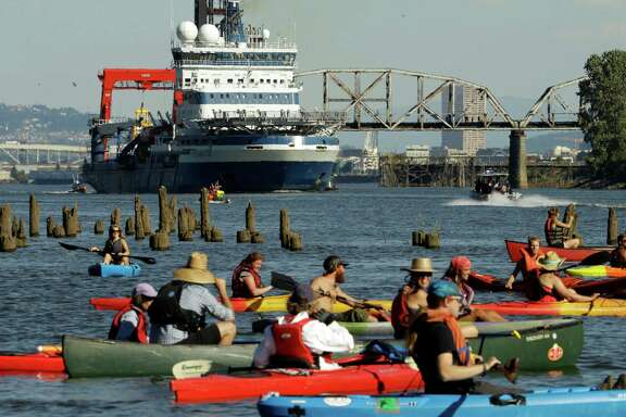 Activist kayakers wait as theThe Royal Dutch Shell PLC icebreaker Fennica heads up the Willamette River on its way to Alaska in Portland, Ore., Thursday, July 30, 2015.  (AP Photo/Don Ryan)