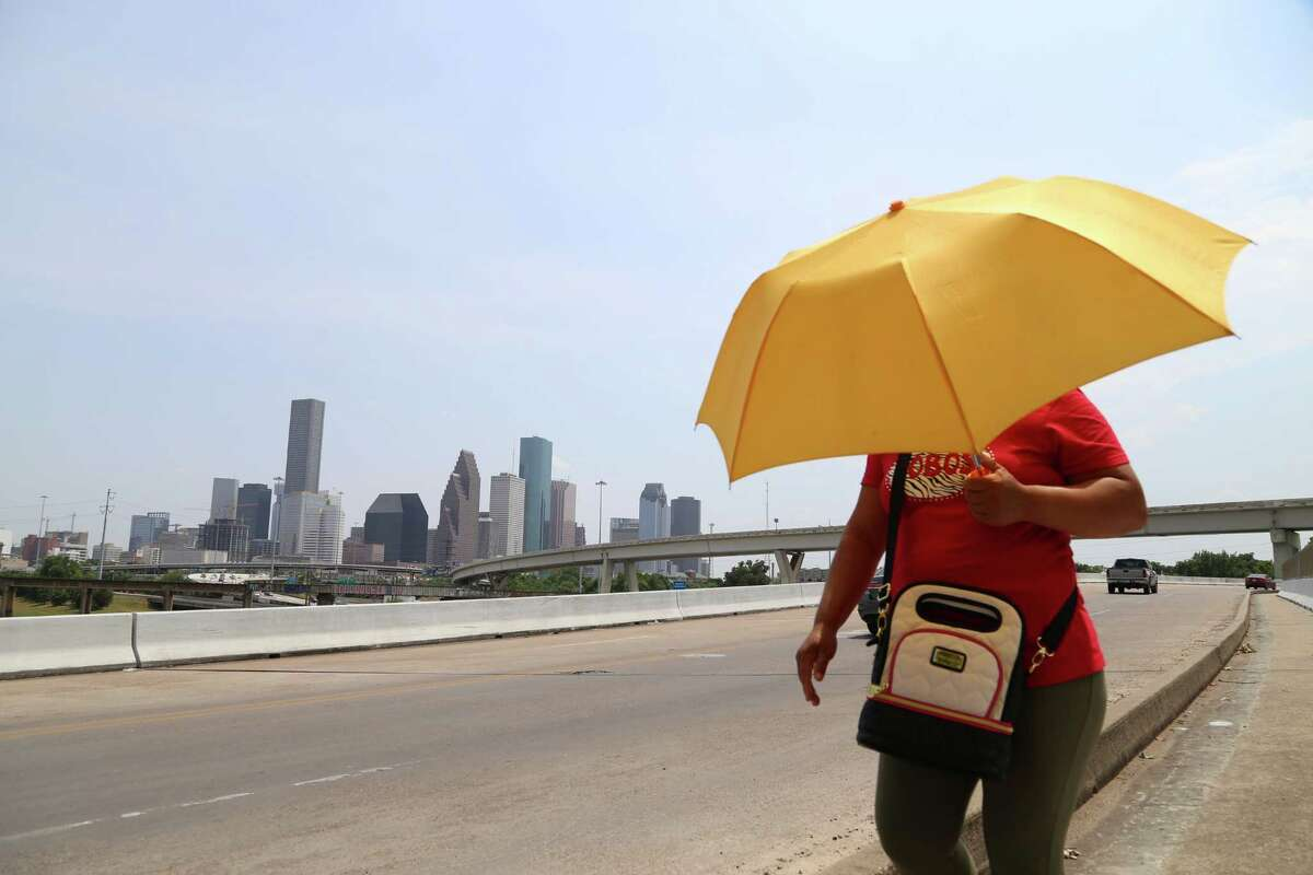 A Houstonian carries an umbrella to keep shade from the unforgiving sun while she crosses the Hogan Street Bridge over White Oak Bayou, north of downtown. Thursday, July 30, 2015, in Houston.