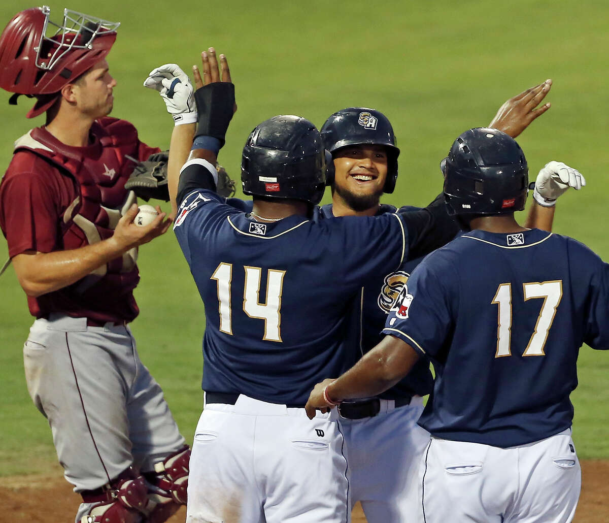 Missions' Diego Goris (center) celebrates with teammates Yeison Asencio (center left) and Duanel Jones after hitting a three-run homer as RoughRiders' Patrick Cantwell (left) looks on during the fifth inning Thursday July 30, 2015 at Nelson W. Wolff Municipal Stadium.