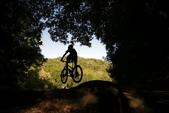 A biker does a jump at Deer Park during Otis Guy Mountain Bike Camp in Fairfax, Calif., on Tuesday, July 28, 2015.