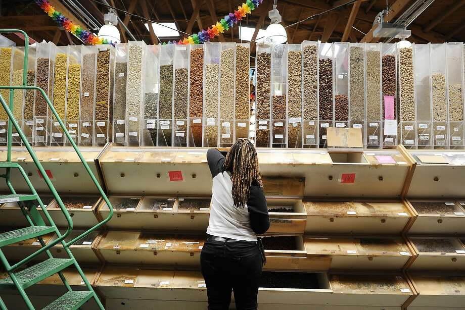 Molly Eaton refills containers in the bulk department at Rainbow Grocery in San Francisco. Started in 1975, the worker-owned food co-op is celebrating its 40th anniversary this year. Photo: Michael Short, Special To The Chronicle