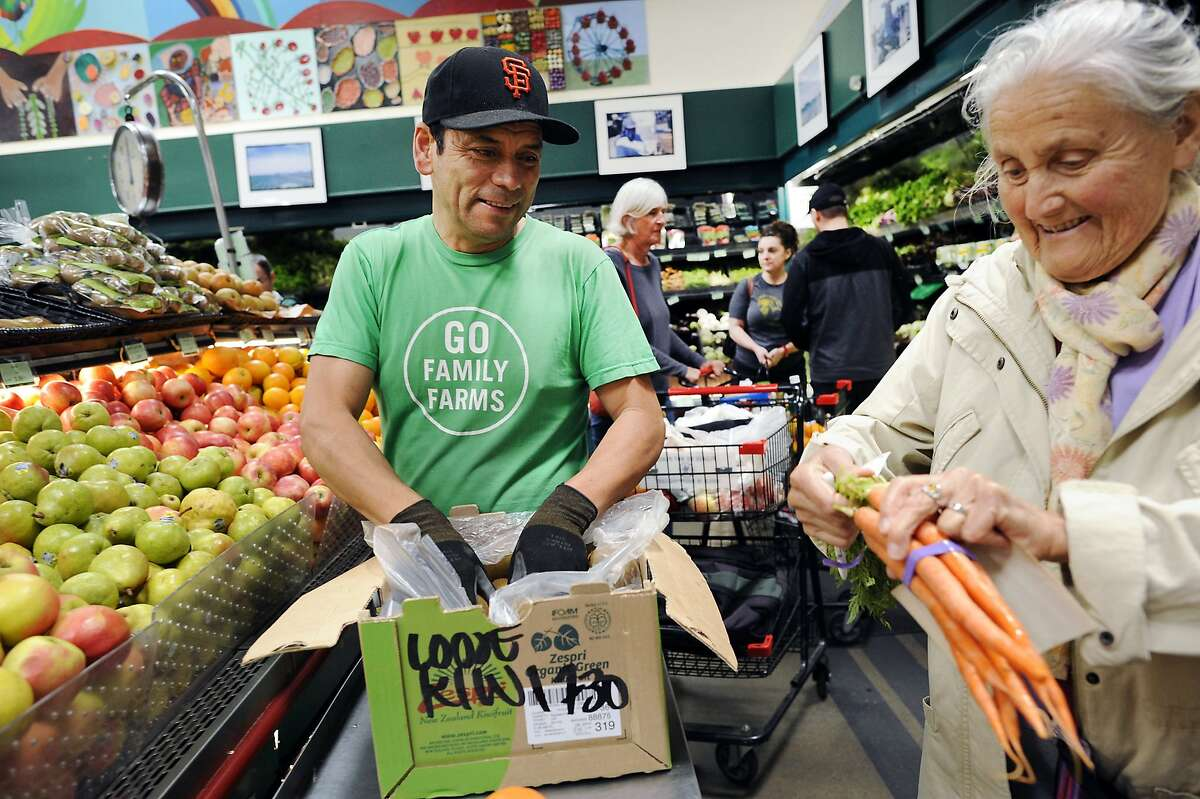 Ricardo Cartagena stocks kiwis in the produce department as Pia Esposito, who has been a customer for over 35 years, selects a bunch of carrots at Rainbow Grocery in San Francisco, CA Sunday, July 30, 2015. Started in 1975, worker owned food co-op Rainbow Grocery is celebrating it's 40th anniversary this year.