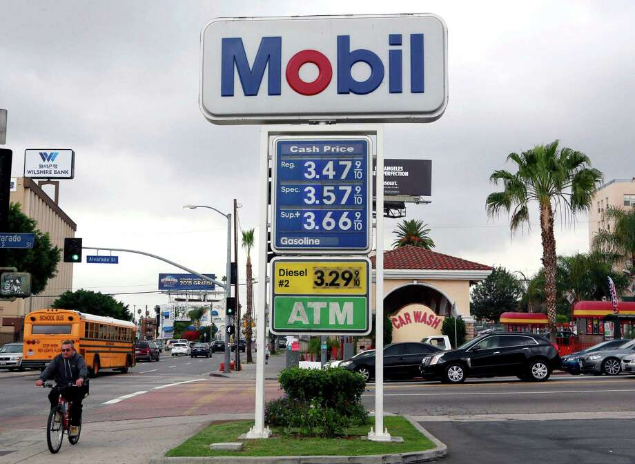 FILE - In this Feb. 27, 2015, file photo, a cyclist rides by a Mobil gas station in Los Angeles. Exxon Mobil Corp. reports quarterly financial results on Friday, July 31, 2015. (AP Photo/Nick Ut, File) Photo: Nick Ut, STF / AP