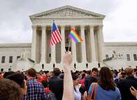 In this Friday June 26, 2015, file photo, a man holds a U.S. and a rainbow flag outside the Supreme Court in Washington after the court legalized gay marriage nationwide.
