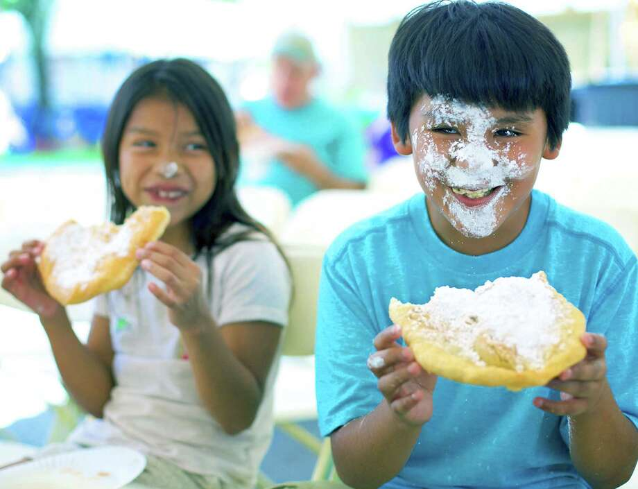 Lizzy Tietjen, 8, appears to have her own issues with sugar on her nose, yet she gets a kick out of the mess made by her brother, Nate, 10, with fried dough straight from the Rotary Club's concession van during the Greater New Milford Chamber of Commerce's annual Village Fair Days on the Village Green. July 24, 2015 Photo: Trish Haldin / Trish Haldin / The News-Times Freelance