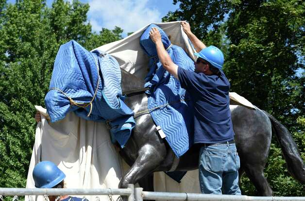 A worker from the Bonacio Construction covers the statue of Native Dancer with a jockey after it was lowered in to it's permanent placement atop the pedestal at the top of Congress Park Friday July 31, 2015 in Saratoga Springs, N.Y.    (Skip Dickstein/Times Union) Photo: SKIP DICKSTEIN / 10032844A