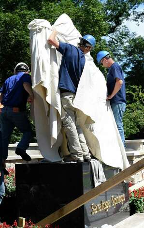 Workers from the Bonacio Construction cover the statue of Native Dancer with a jockey after it was lowered in to it's permanent placement atop the pedestal at the top of Congress Park Friday July 31, 2015 in Saratoga Springs, N.Y.    (Skip Dickstein/Times Union) Photo: SKIP DICKSTEIN / 10032844A
