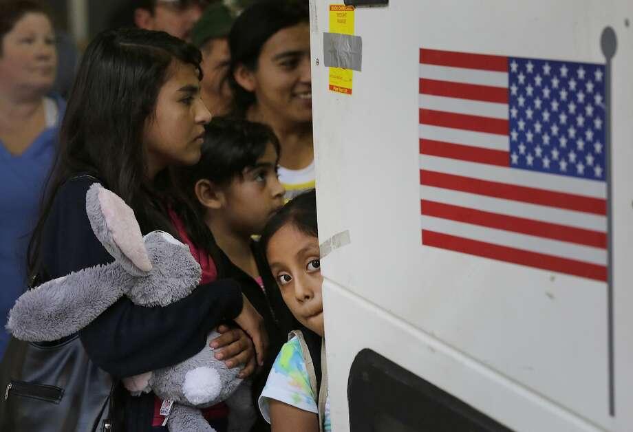Immigrants from El Salvador and Guatemala board a bus after they were released from a detention center in San Antonio. Photo: Eric Gay, Associated Press