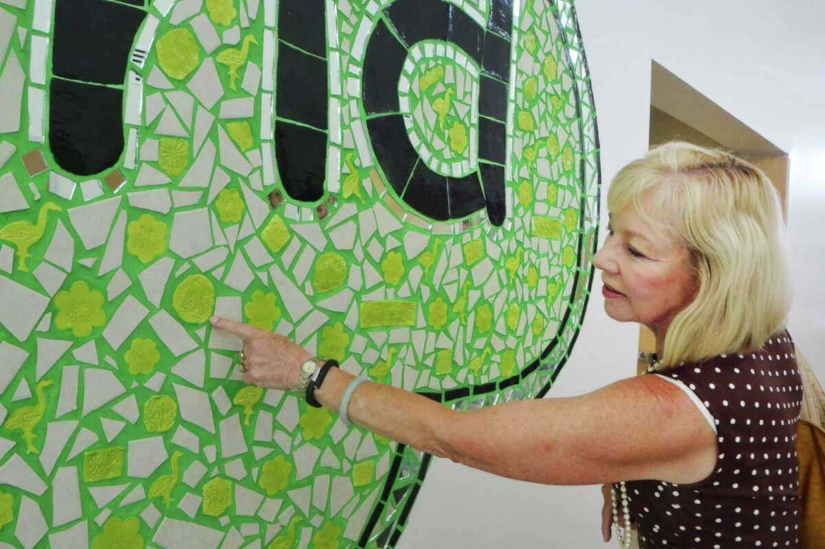 Stratford Superintendent Janet Robinson points to the mosiac mural created by Ben's Bells, the Soto family's own touch to the Victoria Soto School in Stratford. The mosiac includes green flamingo tiles, a beloved animal of Soto and the common symbol of Team Victoria Soto. The new school is shown in photos below.