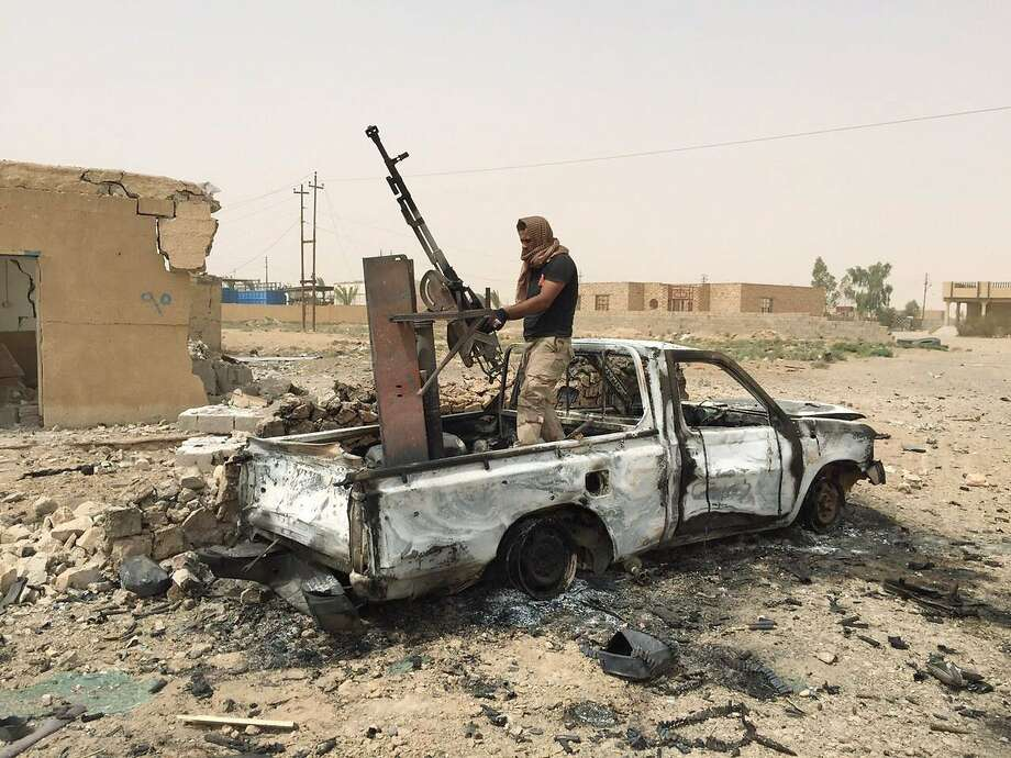 An Iraqi soldier dismantles a weapon from an Islamic State vehicle after a U.S. air strike. Photo: Uncredited, Associated Press
