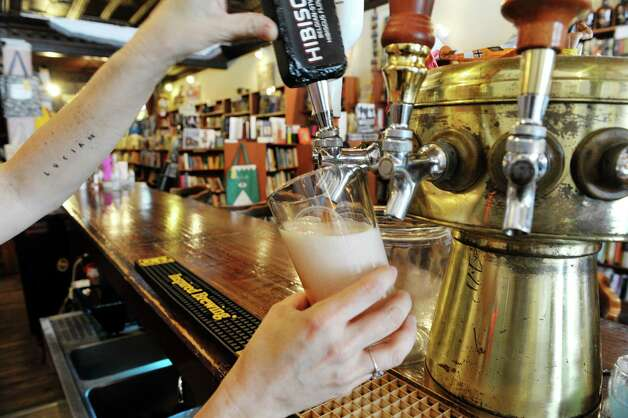 A beer on tap is poured inside the Spotty Dog Books & Ale store on Warren St. on Thursday, June 25, 2015, in Hudson, N.Y.  Patrons can get a beer while shopping for books or art supplies.   (Paul Buckowski / Times Union) Photo: PAUL BUCKOWSKI / 00032353A